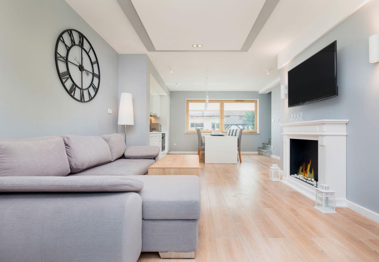 Sofa, Uhr, Lampe, Kamin, Fernseher, Essbereich, Esstisch, Stühle, Küchenzeile, Backofen, Mikrowelle, Fenster