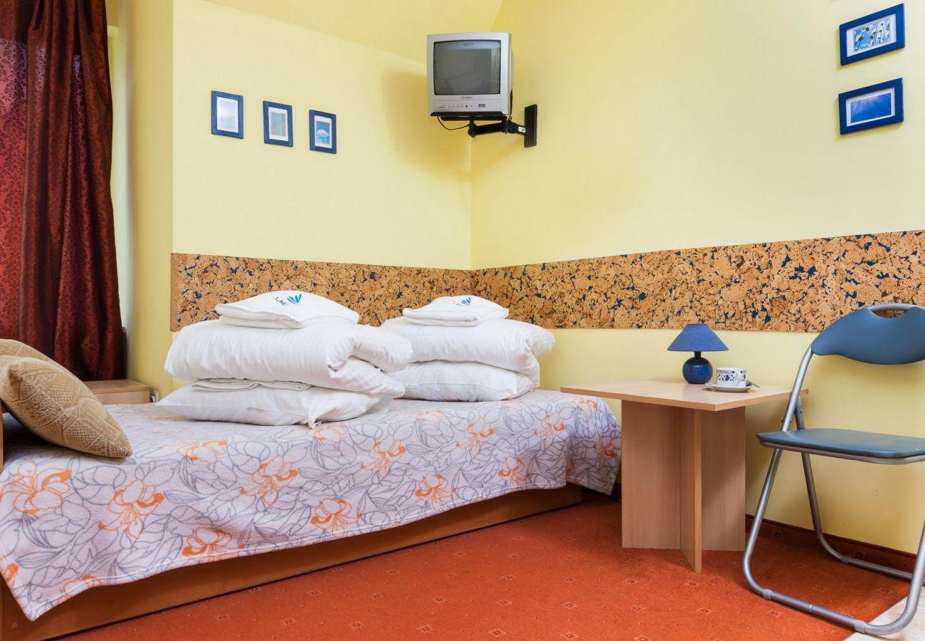 living room, tv, single bed, sofa, night stand, night lamp