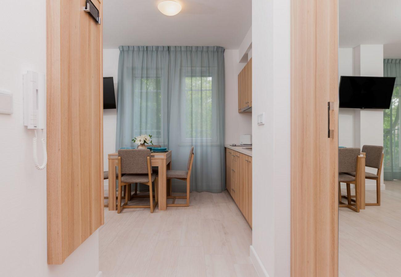 korytarz, szafa, lustro, TV, stół, krzesła, aneks kuchenny, okno