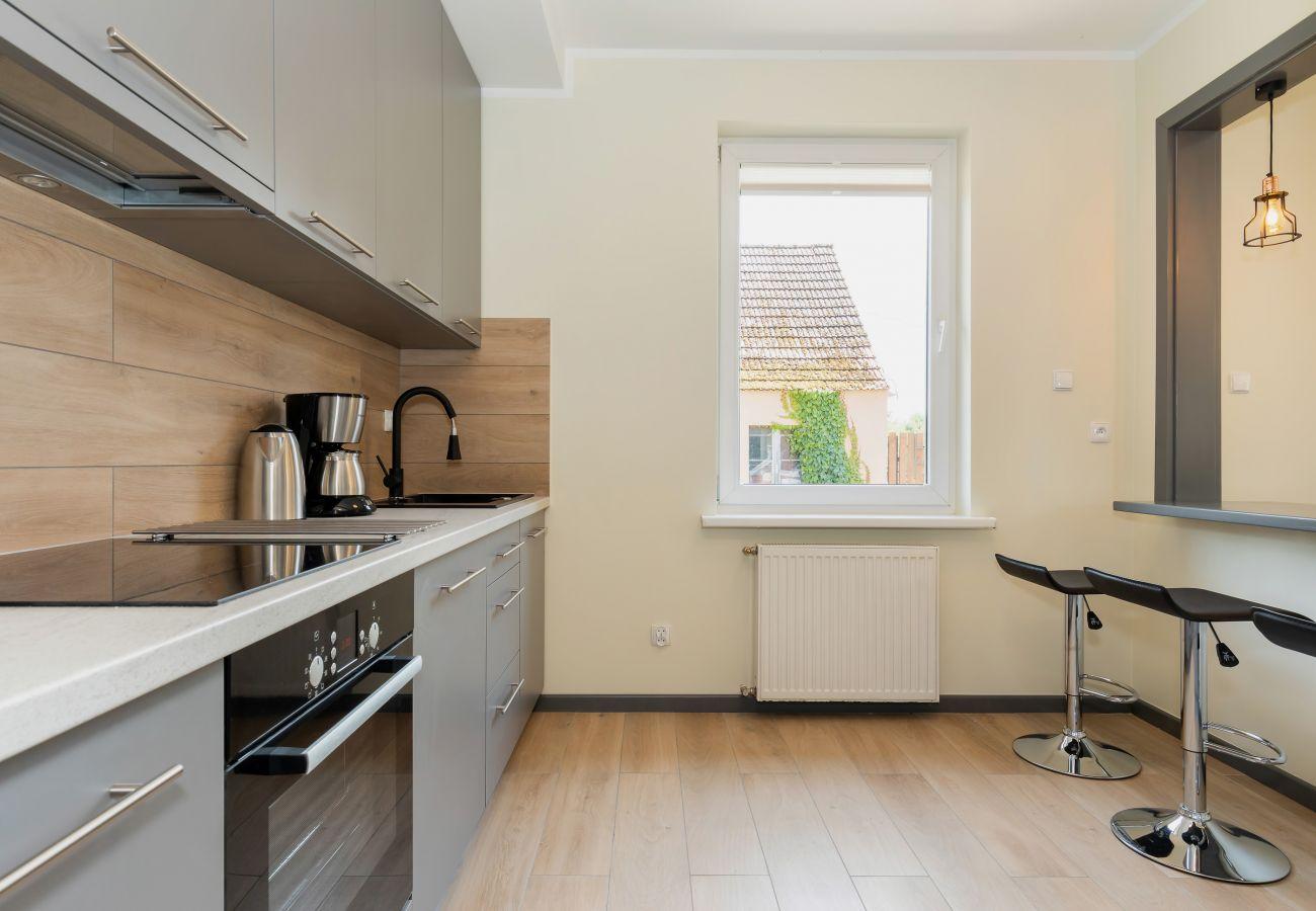 aneks kuchenny, krzesła barowe, okno, szafki kuchenne, piekarnik, ekspres do kawy