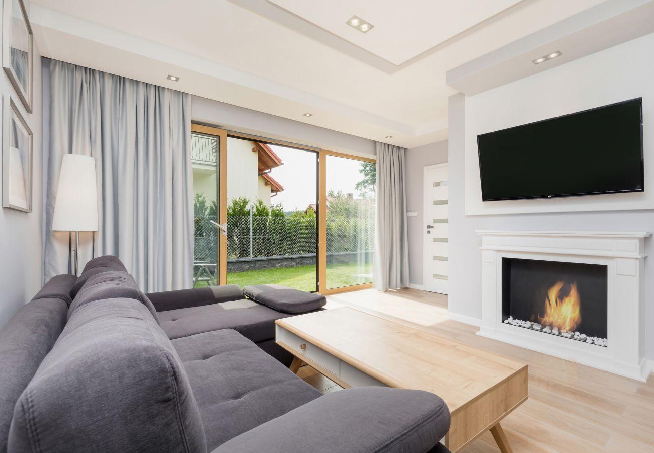 pokój dzienny, telewizor, kominek, sofa, stolik kawowy, widok na zewnątrz, lampa, wynajem