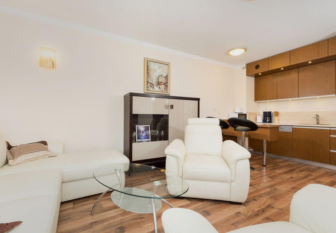pokój dzienny, fotel, sofa, stolik kawowy, telewizor, aneks kuchenny, jadalnia, wynajem