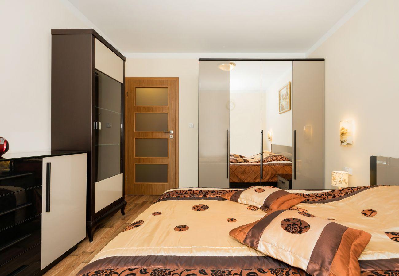 sypialnia, podwójne łóżko, szafka nocna, lampa, zegar, szafa, okno, wynajem