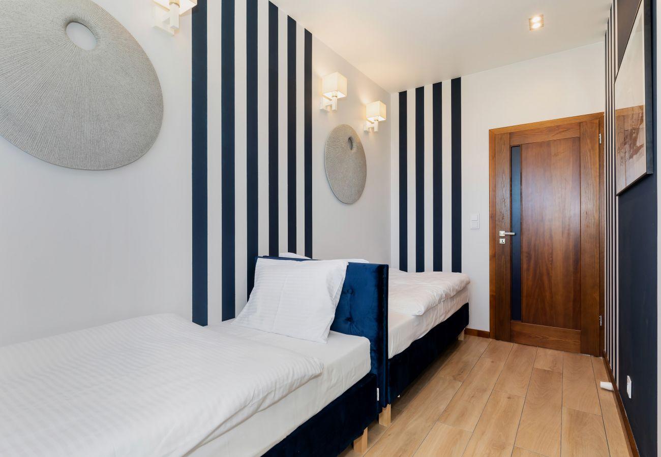 sypialnia, łóżka pojedyncze, pościel, poduszki, szafa, lustro, wynajem