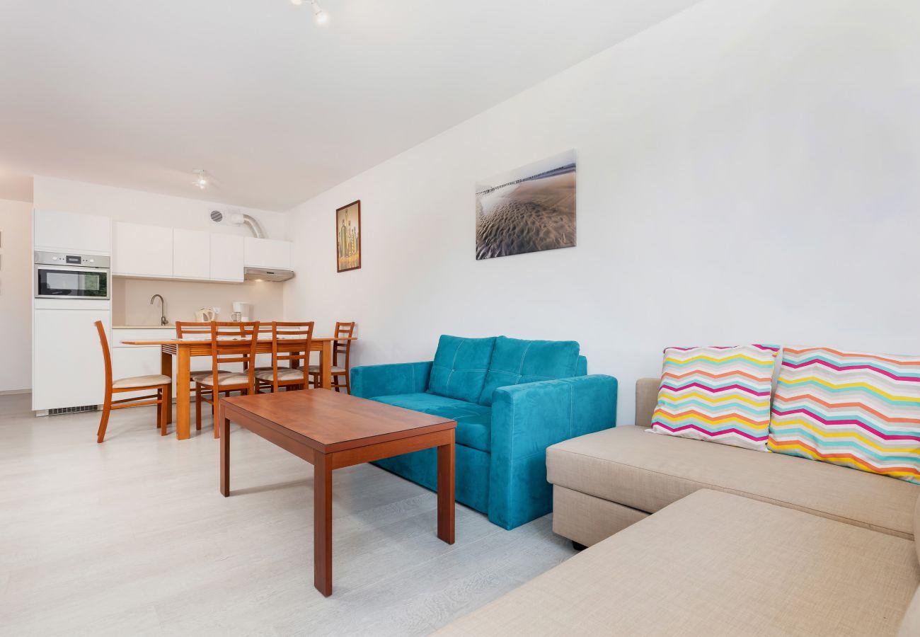 salon, sofa, telewizor, stolik kawowy, stół, jadalnia, krzesła, aneks kuchenny, piekarnik, czajnik, ekspres do kawy, wynajem