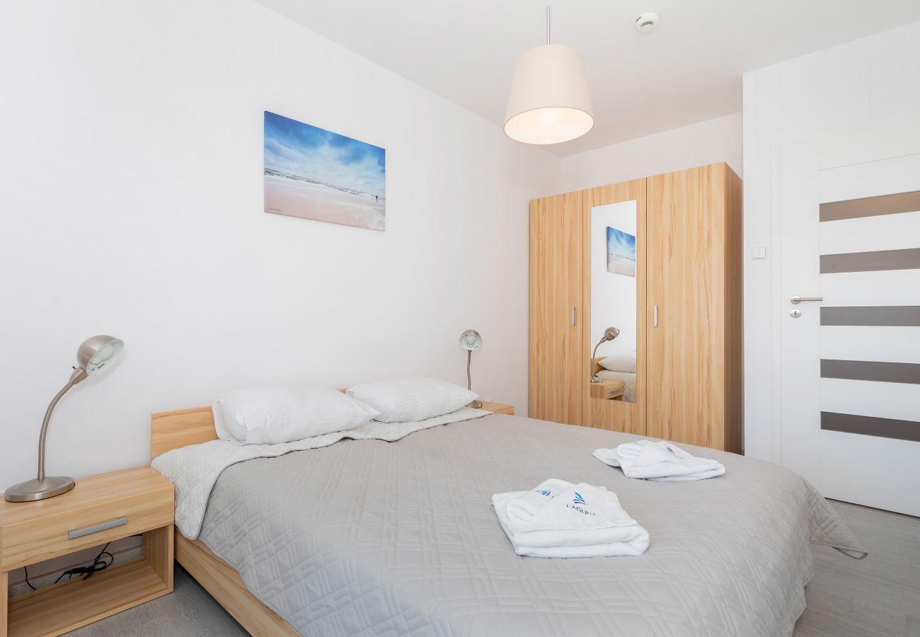 sypialnia, podwójne łóżko, pościel, poduszki, ręczniki, szafa, lustro, szafka nocna, lampka nocna, wynajem
