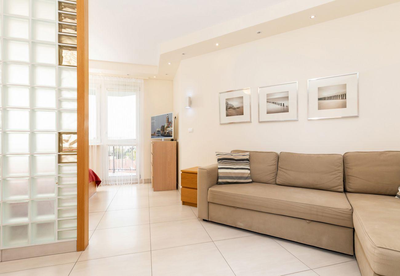 salon, sofa, poduszki, telewizor, aneks kuchenny, sypialnia, jadalnia, stół, krzesła, wynajem
