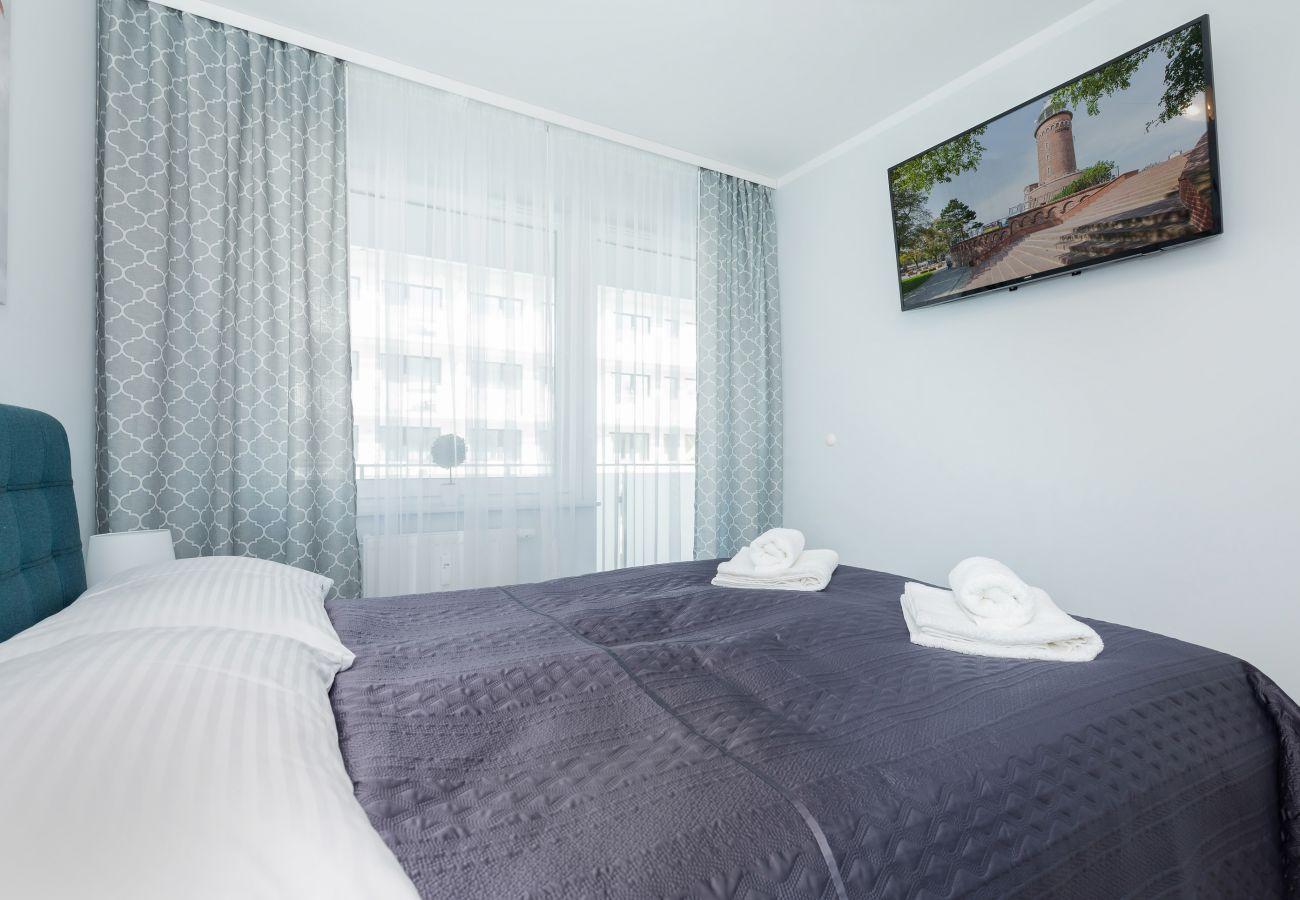 sypialnia, podwójne łóżko, szafka nocna, lampka nocna, szafa, telewizor, pościel, poduszki, mieszkanie, wnętrze, wynajem