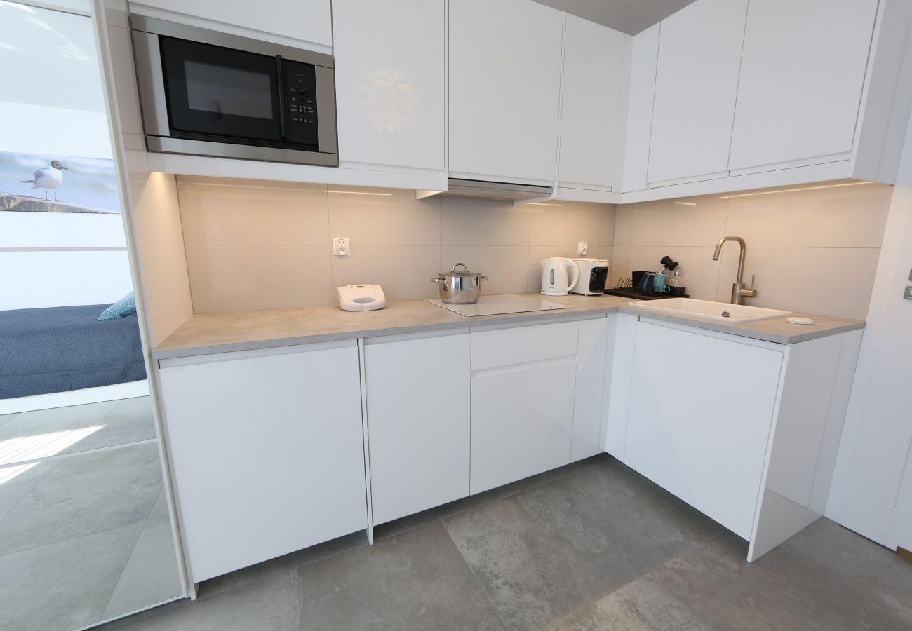 kuchnia, aneks kuchenny, kuchenka, zmywarka do naczyń, czajnik, ekspres do kawy, toster, mikrofalówka, lodówka, szafki, mieszkanie, wnętrze, wynajem
