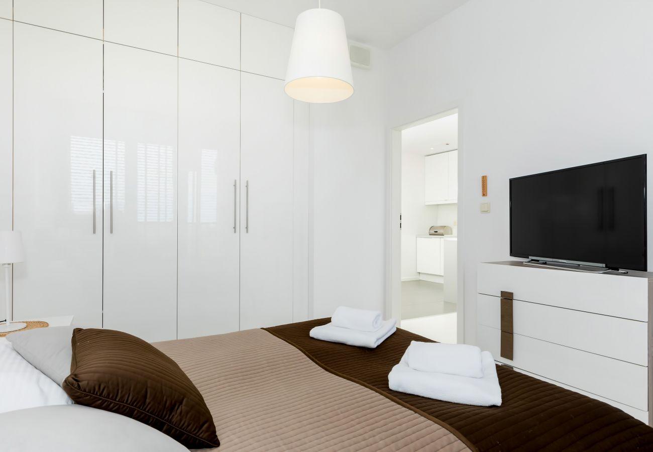 sypialnia, podwójne łóżko, szafka nocna, lampka nocna, szafa, pościel, poduszki, telewizor, mieszkanie, wnętrze, wynajem