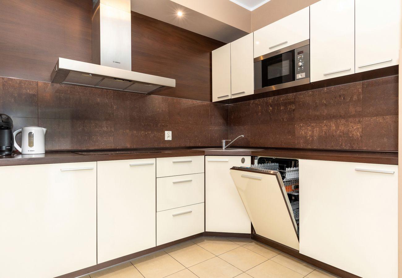 kuchnia, aneks kuchenny, jadalnia, stół, krzesła, kuchenka, zmywarka do naczyń, czajnik, ekspres do kawy, lodówka z zamrażarką, toster, szafki, mieszk