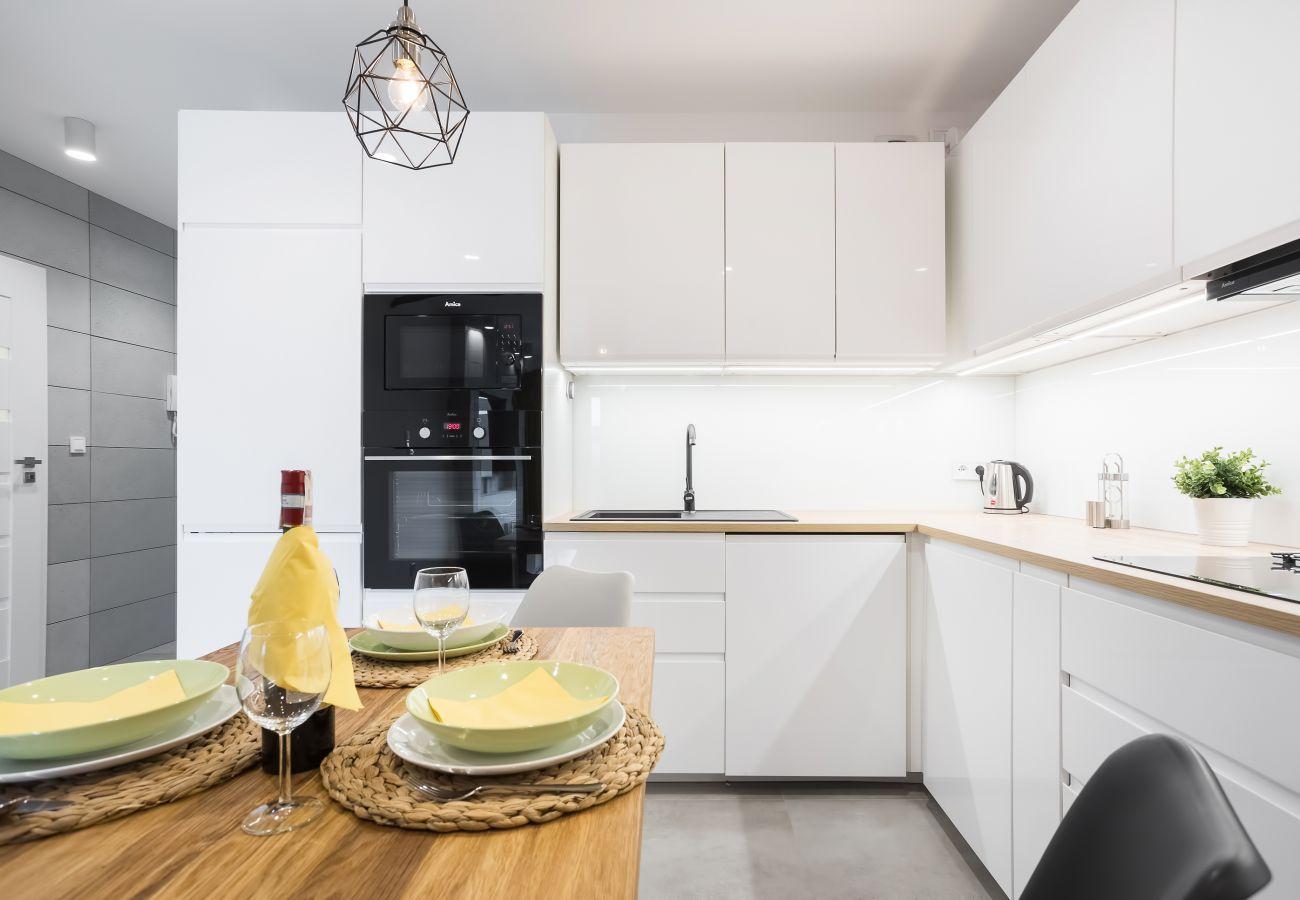 kuchnia, aneks kuchenny, jadalnia, stół, krzesła, kuchenka, lodówka z zamrażarką, zmywarka, piekarnik, czajnik, toster, mikrofalówka, szafki, mieszkan
