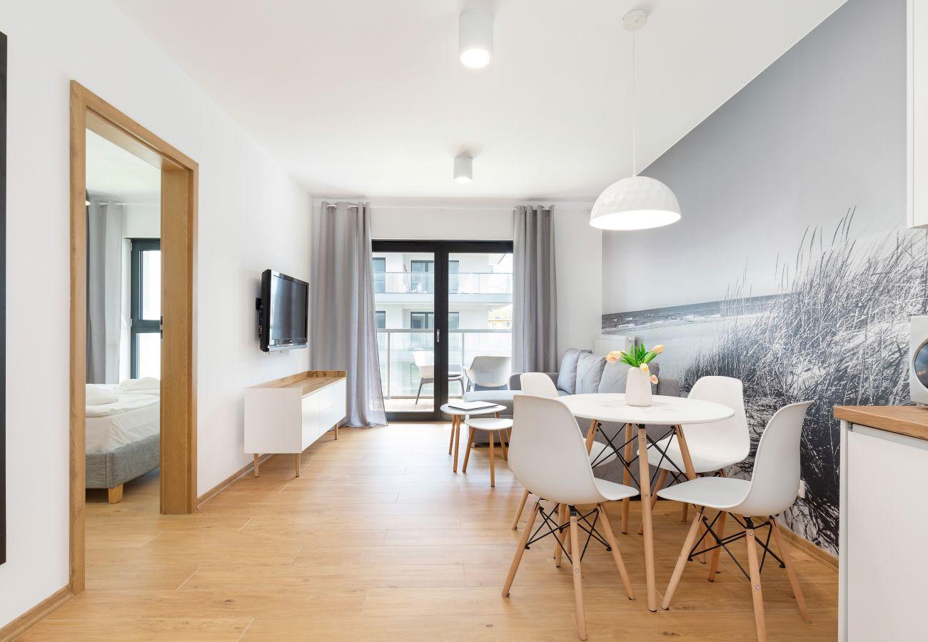 salon, jadalnia, stół, krzesła, sofa, stolik kawowy, telewizor, aneks kuchenny, apartament, wnętrze, wynajem