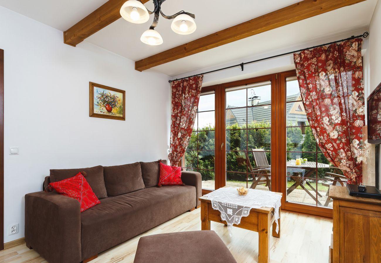 salon, sofa, stolik kawowy, kominek, telewizor, jadalnia, aneks kuchenny, apartament, wnętrze, wynajem