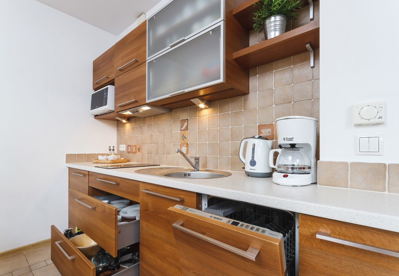 kuchnia, aneks kuchenny, jadalnia, stół, krzesła, kuchenka, ekspres do kawy, czajnik, mikrofalówka, zmywarka, szafki, mieszkanie, wnętrze, wynajem