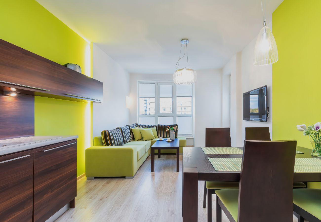 salon, sofa, stolik kawowy, telewizor, aneks kuchenny, jadalnia, stół jadalny, krzesła, apartament, wnętrze, wynajem