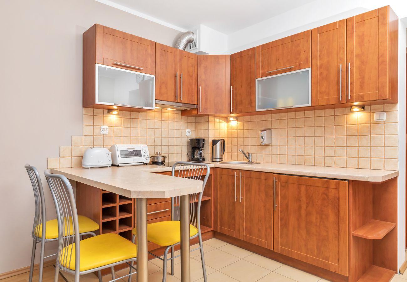 kuchnia, aneks kuchenny, czajnik, ekspres do kawy, piekarnik, lodówka, szafki, jadalnia, wyspa kuchenna, krzesła, studio, wnętrze, wynajem