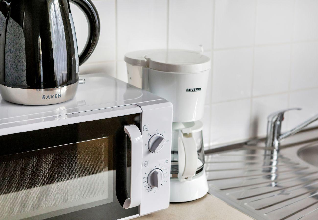 kuchnia, aneks kuchenny, kuchenka elektryczna, czajnik, lodówka z zamrażarką, ekspres do kawy, mikrofalówka, toster, szafki, studio, wnętrze, wynajem